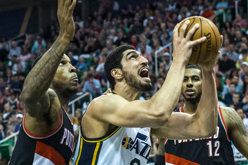 Chris Detrick  |  The Salt Lake Tribune Utah Jazz center Enes Kanter (0) shoots past Portland Trail Blazers forward Thomas Robinson (41) and Portland Trail Blazers forward LaMarcus Aldridge (12) during the game at EnergySolutions Arena Friday April 11, 2014. Portland is winning the game 53-51 at halftime.