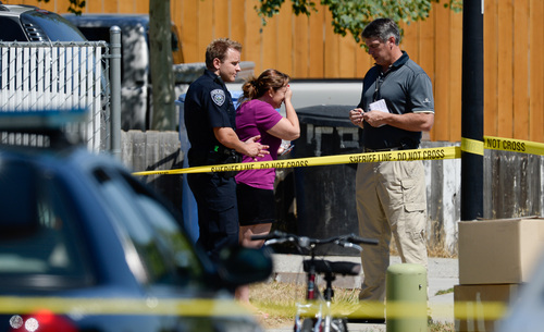 Francisco Kjolseth  |  The Salt Lake Tribune A woman tries to hold back tears as she speaks with Unified Police during an investigation at the scene where one of their officers shot an armed man in Taylorsville on Friday morning, Aug 1, 2014. The man with the gun outside a residence at 5514 S. Ridgecrest (3400 West) was shot at least once and is reported in serious condition.