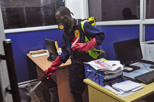 An employee  of the Monrovia City Corporation sprays disinfectant inside a government building in a bid to prevent the spread of  the deadly Ebola virus, in the city of Monrovia, Liberia, Friday, Aug. 1, 2014. U.S. health officials warned Americans not to travel to the three West African countries hit by the worst recorded Ebola outbreak in history. The travel advisory issued Thursday applies to nonessential travel to Guinea, Liberia and Sierra Leone, where the deadly disease has killed more than 700 people this year. (AP Photo/Abbas Dulleh)