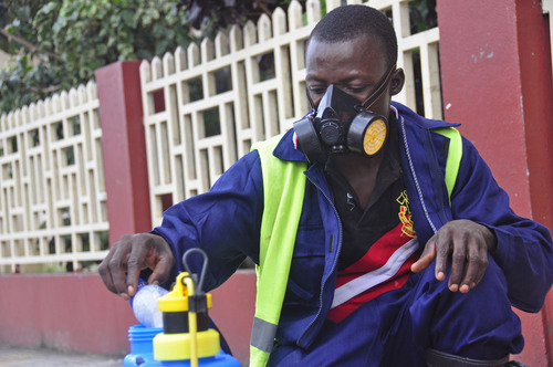 An employee  of the Monrovia City Corporation mixes disinfectant before spraying it on the streets in a bid to prevent the spread of  the deadly Ebola virus, in the city of Monrovia, Liberia, Friday, Aug. 1, 2014. U.S. health officials warned Americans not to travel to the three West African countries hit by the worst recorded Ebola outbreak in history. The travel advisory issued Thursday applies to nonessential travel to Guinea, Liberia and Sierra Leone, where the deadly disease has killed more than 700 people this year. (AP Photo/Abbas Dulleh)