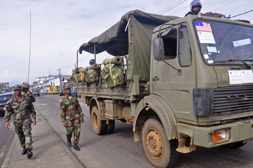 Liberian soldiers walk through streets to prevent panic as fears of the deadly Ebola virus spread in the city of Monrovia, Liberia, Friday, Aug. 1, 2014. U.S. health officials warned Americans not to travel to the three West African countries hit by the worst recorded Ebola outbreak in history. The travel advisory issued Thursday applies to nonessential travel to Guinea, Liberia and Sierra Leone, where the deadly disease has killed more than 700 people this year. (AP Photo/Abbas Dulleh)
