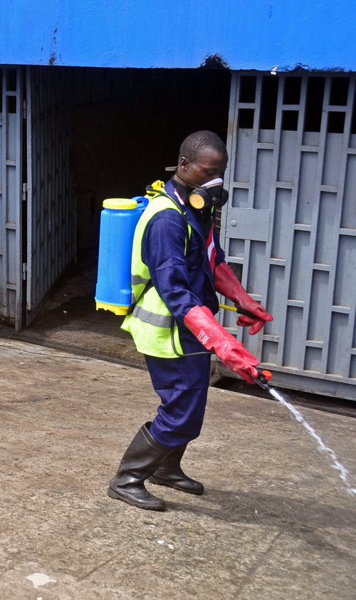 A employee  of the Monrovia City Corporation spray disinfectant on a street in front of a building in a bid to prevent the spread of  the deadly Ebola virus, in the city of Monrovia, Liberia, Friday, Aug. 1, 2014. U.S. health officials warned Americans not to travel to the three West African countries hit by the worst recorded Ebola outbreak in history. The travel advisory issued Thursday applies to nonessential travel to Guinea, Liberia and Sierra Leone, where the deadly disease has killed more than 700 people this year. (AP Photo/Abbas Dulleh)