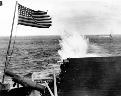 A 1944 photo of the American flag which flies from the U.S. warship U.S. Exessx  as a Japanese bomb explodes in the water off the Philippine Islands during World War II. (AP Photo).