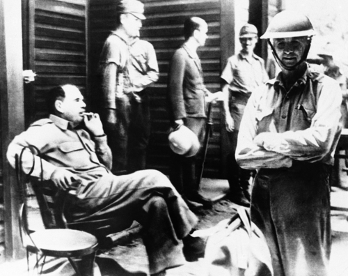 Men are shown in a Japanese prisoner of war camp, after the surrender of American defenders of Corregidor in the Philippines, Aug. 1942.  Major General Jonathan M. Wainwright, who succeeded Gen. MacArthur as officer in charge and who fought to the last, is seen on the right wearing his steel helmet. (AP Photo)
