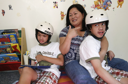 Arlene Aguirre, center, tells stories about her son Carl, as she sits with  Carl's twin brother Clarence, 12, at the family's home in Scarsdale, N.Y., Thursday, July 31, 2014. On Monday, Aug. 4, 2014, Montefiore Hospital and the family will celebrate the 10th anniversary of the risky surgery that separated the boys, who were born as conjoined twins.  (AP Photo/Kathy Willens)