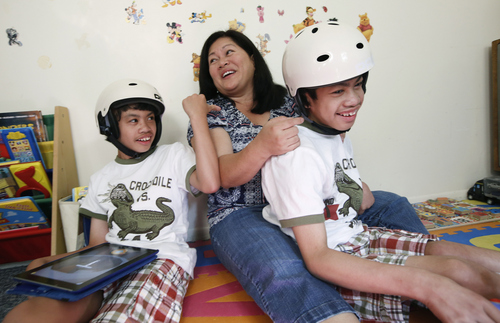 Arlene Aguirre, center, plays with her formerly conjoined twin sons, Clarence, left, and Carl, 12, at the family's home in Scarsdale, N.Y., Thursday, July 31, 2014. On Monday, Aug. 4, the family will celebrate the 10th anniversary of the risky surgery in which the boys were separated at Montefiore Hospital, where the surgery was initially performed. (AP Photo/Kathy Willens)