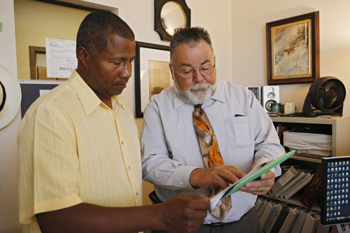 """In this July 8, 2014 photo, William Kistler, right, goes over a clients' information with support specialist Ronald Smith at Kistler's office in Denver. Sixty-three-year-old Kistler views retirement like someone tied to the tracks watching a train coming: It's looming, it's threatening and there's little he can do.""""There is not enough to retire with,"""" said Kistler, a Golden, Colorado, resident who said he is unable to build up a nest egg for his wife with his modest salary helping seniors navigate benefits. """"It's completely frightening to tell you the truth. And I, like a lot of people, try not to think about it too much, which is actually a problem.""""(AP Photo/Ed Andrieski)"""