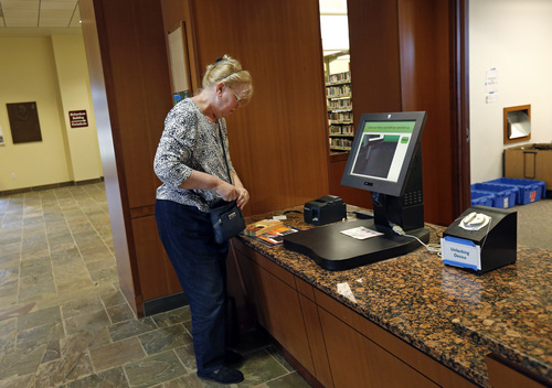 """In this July 7, 2014 photo, Susan McNamara prepares to borrow a book from the public library in Quincy, Mass. She sold her home to meet expenses. """"Over the years, all I've been able to do, especially as a single parent, is just pay your bills every month,"""" said McNamara, a 62-year-old adjunct professor from the Boston area. """"Anything that's left over is used up when your car breaks down or when the furnace breaks down ... There's never anything left over, ever."""" (AP Photo/Elise Amendola)"""