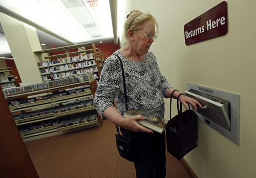"""In this July 7, 2014 photo, Susan McNamara returns a book to the public library in Quincy, Mass. """"Over the years, all I've been able to do, especially as a single parent, is just pay your bills every month,"""" said McNamara, a 62-year-old adjunct professor from the Boston area. """"Anything that's left over is used up when your car breaks down or when the furnace breaks down ... There's never anything left over, ever."""" (AP Photo/Elise Amendola)"""