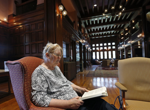 """In this July 7, 2014 photo, Susan McNamara relaxes with a book at her favorite place at the public library in Quincy, Mass. """"Over the years, all I've been able to do, especially as a single parent, is just pay your bills every month,"""" said McNamara, a 62-year-old adjunct professor from the Boston area. """"Anything that's left over is used up when your car breaks down or when the furnace breaks down ... There's never anything left over, ever."""" (AP Photo/Elise Amendola)"""