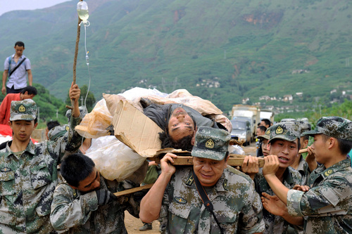 Rescuers carry an injured man during a rescue operation following Sunday's earthquake in Ludian county of Zhaotong city in southwest China's Yunnan Province, Monday, Aug. 4, 2014. Rescuers dug through shattered homes Monday looking for survivors of the strong earthquake that killed hundreds and injured more than a thousand people. (AP Photo/Kyodo News) JAPAN OUT