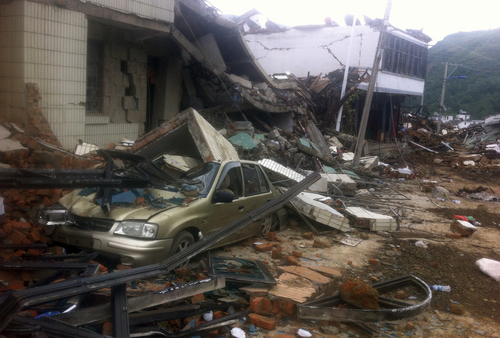 A car is crushed by a collapsed building in the epicenter of an earthquake that struck the town of Longtoushan in Ludian county in southwest China's Yunnan province Monday, Aug. 4, 2014. Rescuers dug through shattered homes Monday looking for survivors of a strong earthquake in southern China's Yunnan province that toppled thousands of homes on Sunday, killing hundreds and injuring more than a thousand people (AP Photo) CHINA OUT