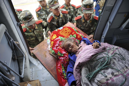 In this photo released by China's Xinhua News Agency, rescuers convey an injured person in the quake-hit Longtoushan Town of Ludian County in Zhaotong city, southwest China's Yunnan Province, Monday, Aug. 4, 2014.  Rescuers dug through shattered homes Monday looking for survivors of a strong earthquake in southern province as the death toll rose to hundreds of people, with more than a thousand injured.(AP Photo/Xinhua, Xue Yubin) NO SALES