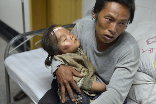 A man holds an injured child receiving medical treatment at a hospital following an earthquake in Ludian county in southwest China's Yunnan province Monday, Aug. 4, 2014. A strong earthquake in southern China's Yunnan province toppled thousands of homes on Sunday, killing hundreds and injuring more than a thousand people. (AP Photo) CHINA OUT