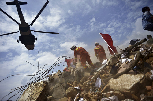A helicopter flies over rescue workers at the epicenter of Sunday's earthquake that struck the town of Longtoushan in Ludian County in southwest China's Yunnan Province, Monday, Aug. 4, 2014. Rescuers dug through shattered homes Monday looking for survivors of the strong earthquake that toppled thousands of homes, killed hundreds and injured more than a thousand people. (AP Photo)