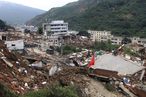 Rescue workers search for survivors among the remains of collapsed buildings in the epicenter of an earthquake that struck the town of Longtoushan in Ludian county in southwest China's Yunnan province Monday, Aug. 4, 2014. Rescuers dug through shattered homes Monday looking for survivors of the strong earthquake that toppled thousands of homes on Sunday, killing hundreds and injuring more than a thousand people. (AP Photo) CHINA OUT