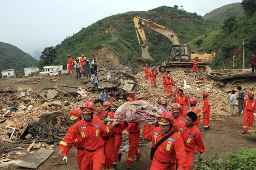 Rescue workers remove a dead body from the remains of a collapsed building at the epicenter of an earthquake that struck the town of Longtoushan in Ludian county in southwest China's Yunnan province Monday, Aug. 4, 2014.  Rescuers dug through shattered homes Monday looking for survivors of a strong earthquake in southern China's Yunnan province that toppled thousands of homes on Sunday, killing hundreds and injuring more than a thousand people. (AP Photo) CHINA OUT