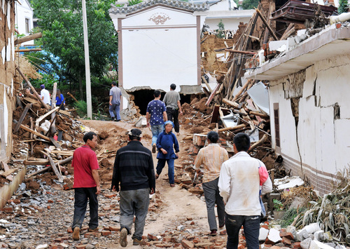 People walk by collapsed houses  after Sunday's earthquake in Ludian County of Zhaotong City in southwest China's Yunnan Province, Monday, Aug. 4, 2014. Rescuers dug through shattered homes Monday looking for survivors of a strong earthquake in southern China's Yunnan province that killed hundreds and injured more than a thousand people. (AP Photo/Kyodo News) JAPAN OUT