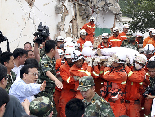 Chinese Premier Li Keqiang helps make way for the injured at the earthquake zone in the town of Longtoushan in Ludian County in southwest China's Yunnan Province Monday, Aug. 4, 2014. Li walked into Longtoushan township of Ludian County Monday to examined the situation of the earthquake and instructed the quake relief work. (AP Photop/Xinhua, Yao Dawei) NO SALES