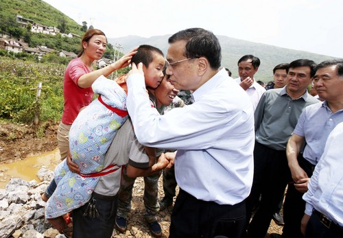 Chinese Premier Li Keqiang comforts a child at the earthquake zone in the town of Longtoushan in Ludian County in southwest China's Yunnan Province Monday, Aug. 4, 2014. Li walked into the worst-hit Longtoushan   Monday to examined the situation of the earthquake and instructed the quake relief work. (AP Photop/Xinhua, Yao Dawei) NO SALES