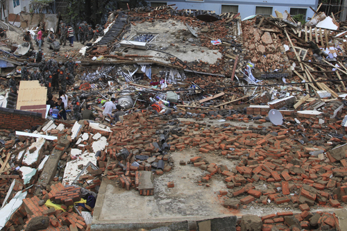 Rescue workers search for survivors amongst the remains of collapsed buildings in the epicenter of an earthquake that struck the town of Longtoushan in Ludian county in southwest China's Yunnan province Monday, Aug. 4, 2014. Rescuers dug through shattered homes Monday looking for survivors of the strong earthquake that toppled thousands of homes on Sunday, killing hundreds and injuring more than a thousand people. (AP Photo) CHINA OUT