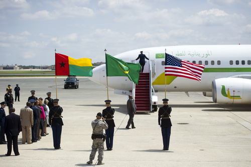 State Department, Air Force, Army and Secret Services members wait for the door to open on President Mohamed Ould Abdel Aziz of Mauritania's airplane at Andrews Air Force Base, Md., Monday, Aug. 4, 2014. President Barack Obama is gathering nearly 50 African heads of state in Washington for the US Africa Summit. (AP Photo/Cliff Owen)