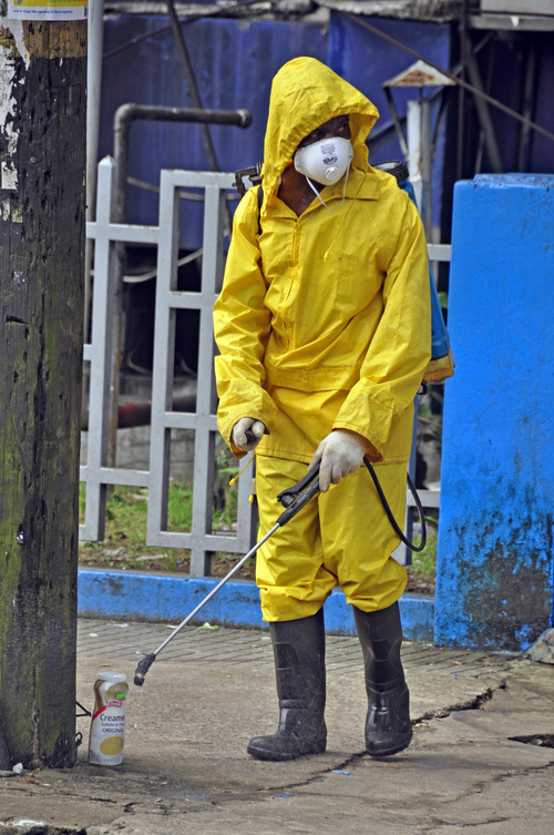 An employee  of the Monrovia City Corporation sprays disinfectant on a street, in front of a building in a bid to prevent the spread of  the deadly Ebola virus, in the city of Monrovia, Liberia, Friday, Aug. 1, 2014 .U.S. health officials warned Americans not to travel to the three West African countries hit by the worst recorded Ebola outbreak in history. The travel advisory issued Thursday applies to nonessential travel to Guinea, Liberia and Sierra Leone, where the deadly disease has killed more than 700 people this year. (AP Photo/Abbas Dulleh)
