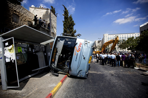 A damaged bus flipped over after attack in Jerusalem, Monday, Aug. 4, 2014. An Israeli-declared cease-fire and troop withdrawals slowed violence in the Gaza war Monday, though an attack on Israeli bus that killed one person in Jerusalem underscored the tensions still simmering in the region. (AP Photo/Sebastian Scheiner)