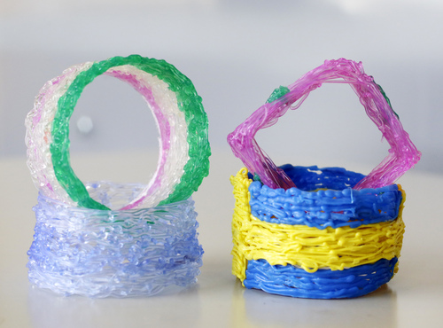 This Tuesday, July 29, 2014 photo shows an assortment of napkin rings made with the 3Doodler, arranged for a photo in New York. A stick of plastic goes in one end of the glue gun-like device and comes out, melted, at the tip. As you move your hand, it leaves a thin trail of cooling, solidifying plastic. Move it around with a plan, laying down string upon string, and things start taking shape.  (AP Photo/Mark Lennihan)