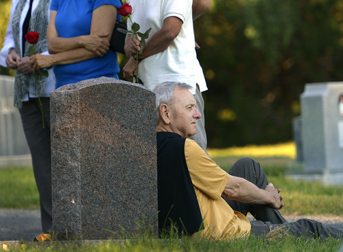 Leah Hogsten     The Salt Lake Tribune Longtime friend and colleague Norman Council rests against Brooke Hopkins' headstone while paying his respects with Peggy Battin and friends. Peggy Battin and friends read poetry and tell loving stories of her husband Brooke Hopkins' July 30, 2014 in the Salt Lake City Cemetery on the eve of the one-year anniversary of his passing. Hopkins battled through pain after a paralyzing 2008 bicycle injury to keep writing, resume teaching while enduring constant pain, infections and setbacks.