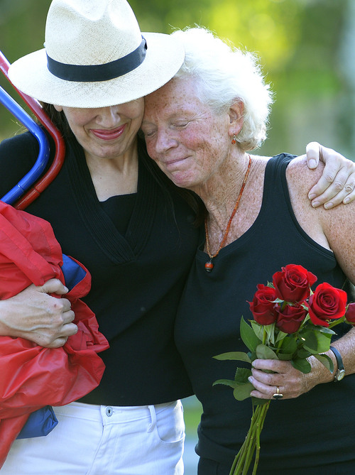 Leah Hogsten  |  The Salt Lake Tribune l-r Lani Poulson Rudick hugs Peggy Battin as they approach Brooke Hopkins' grave. Peggy Battin and friends read poetry and tell loving stories of her husband Brooke Hopkins' July 30, 2014 in the Salt Lake City Cemetery on the eve of the one-year anniversary of his passing. Hopkins battled through pain after a paralyzing 2008 bicycle injury to keep writing, resume teaching while enduring constant pain, infections and setbacks.