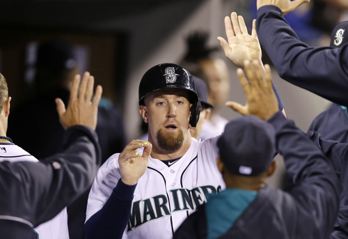 Seattle Mariners' John Buck is congratulated after scoring against the Texas Rangers in a baseball game Saturday, June 14, 2014, in Seattle. (AP Photo/Elaine Thompson)