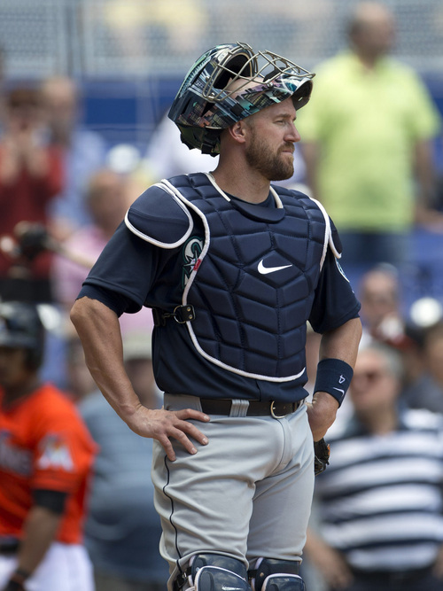 Seattle Mariners catcher John Buch reacts after an electronic review of a home plate play changed the official ruling from an out to a run scored for the Miami Marlins during the eighth inning of a baseball game in Miami, Sunday, April 20,2014. The Marlins won 3-2. (AP Photo/J Pat Carter)