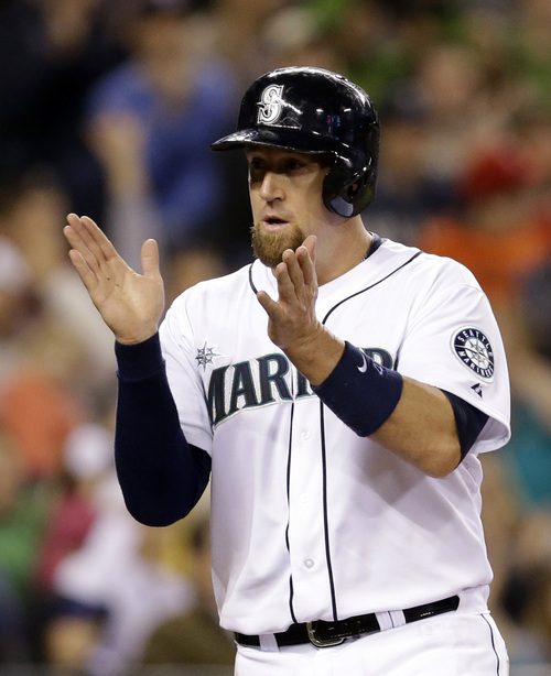 Seattle Mariners' John Buck reacts after scoring against the Texas Rangers in a baseball game Saturday, June 14, 2014, in Seattle. (AP Photo/Elaine Thompson)