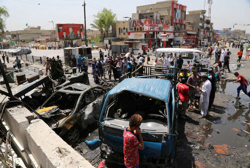 Civilians inspect the site of a car bombing in Baghdad, Iraq, Friday, Aug. 1, 2014. The United Nations says more than 1,700 people, mostly civilians, were killed in Iraq in July, marking a dramatic decline from the previous month, when some 2,400 people were killed as Sunni militants swept across large parts of the country, capturing the second largest city Mosul.(AP Photo/Karim Kadim)