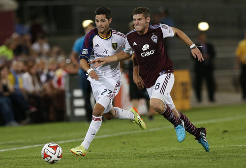 Real Salt Lake midfielder John Stertzer, left, pursues the ball with Colorado Rapids midfielder Dillon Powers in the second half of Salt Lake's 1-0 victory in an MLS soccer game in Commerce City, Colo., on Saturday, Aug. 2, 2014. (AP Photo/David Zalubowski)