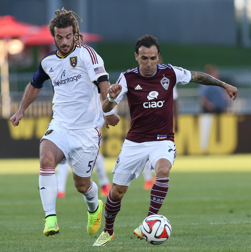 Real Salt Lake midfielder Kyle Beckerman, left, and Colorado Rapids forward Vicente Sanchez compete for the ball in the first half of an MLS soccer game in Commerce City, Colo., on Saturday, Aug. 2, 2014. (AP Photo/David Zalubowski)