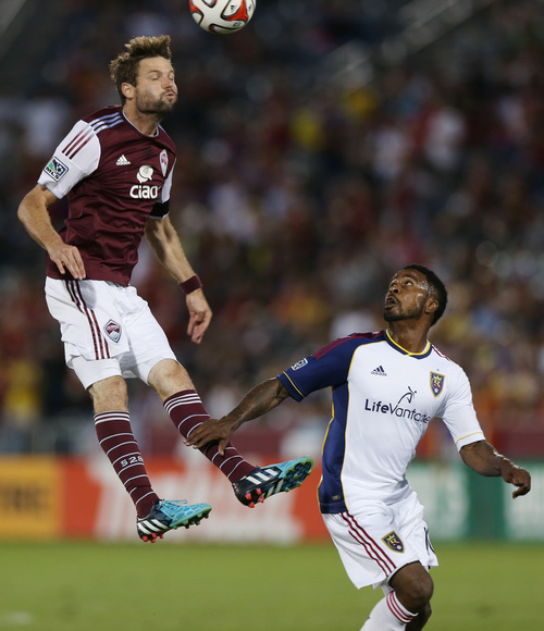 Colorado Rapids defenseman Drew Moor, left, heads ball as Real Salt Lake forward Robbie Findley covers in Salt Lake's 1-0 victory in an MLS soccer game in Commerce City, Colo., on Saturday, Aug. 2, 2014. With the win, Real Salt Lake claimed the Rocky Mountain Cup, which is awarded to the winner of the teams' regular-season schedule. (AP Photo/David Zalubowski)