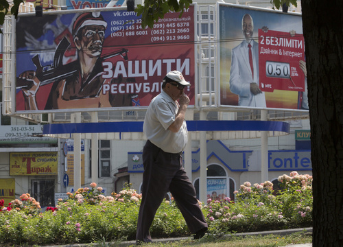 A man walks past a pro-Russian rebels army's agitation poster, left, in the city of Donetsk, eastern Ukraine, Monday, Aug. 4, 2014. The poster reads 'Protect the Republic!'. (AP Photo/Dmitry Lovetsky)