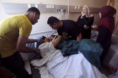 Mohammed al-Bakri brings the body of his three-year-old son Kamal to the boy's wounded mother, Dua, at the Shifa hospital in Gaza City, Tuesday, Aug. 5, 2014. The boy was killed Monday along with two other family members in an Israeli missile strike on their home in Shati refugee camp, Gaza City. (AP Photo/Hatem Moussa)