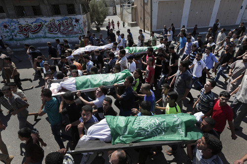 FILE - In this Monday, Aug. 4, 2014 file photo, Palestinian mourners carry the bodies of members of the Najam family during their funeral in Beit Lahiya, Gaza Strip. Seven members of the Najam family, including a 90-year-old man and at least two children, perished in Sunday night's Israeli airstrike. (AP Photo/Lefteris Pitarakis, File)