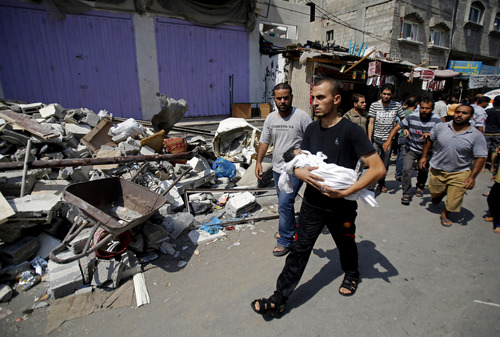 A Palestinian relative carries the body of 4 month-old Asma al-Bakri during her funeral in Gaza City, Tuesday, Aug. 5, 2014. The girl was killed Monday along with two other family members in an Israeli missile strike on their home in Shati refugee camp, Gaza City. (AP Photo/Hatem Moussa)
