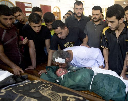 Al-Bakri family members mourn for three year-old Kamal and two other family members during their funeral in Gaza City, Monday, Aug. 5, 2014. The boy was killed along with two other family members in an Israeli missile strike on their home in the Shati refugee camp, Gaza City, on Monday. (AP Photo/Dusan Vranic)