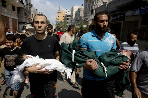 Al-Bakin family members carry the bodies of three year-old Kamal and four month-old Asthm during their funeral in Gaza City, Monday, Aug. 5, 2014. The children were killed along with another family member in an Israeli missile strike on their home in the Shati refugee camp, Gaza City, on Monday.  (AP Photo/Dusan Vranic)