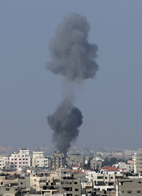 Smoke rises over Gaza City, in northern Gaza Strip, after an Israeli strike, minutes before 8 a.m. (0500 GMT), the time agreed for a preliminary 72-hour cease-fire, on Tuesday Aug, 5, 2014. Israel and Hamas on Monday accepted an Egyptian cease-fire proposal meant to halt a bruising month-long war that has claimed nearly 1,900 Palestinian lives, raising hopes that the bloodiest round of fighting between the bitter enemies could finally be coming to an end. (AP Photo/Lefteris Pitarakis)
