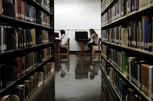 FILE - In this Friday, Oct. 19, 2012 photo, students study in a library on the campus of California State University, Long Beach in Long Beach, Calif. Standard and Poor's estimates that economy could grow at an additional 1 percent a year, or $185 billion annually, if the share of Americans pursuing additional schooling increased at the same average as 15 years ago. (AP Photo/Jae C. Hong)