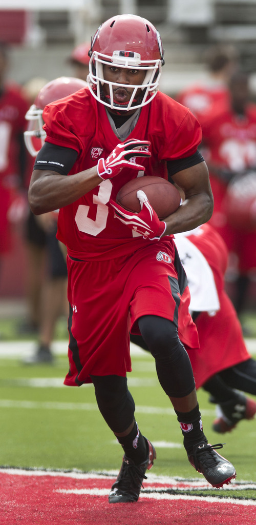 Steve Griffin  |  The Salt Lake Tribune   Utah running back Bubba Poole runs through a hole during football practice at Rice Eccles Stadium in Salt Lake City, Utah Monday, August 4, 2014.