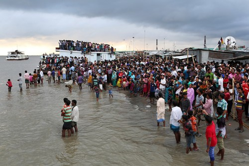 People gather on the banks of  the River Padma after a passenger ferry capsized in Munshiganj district, Bangladesh, Monday, Aug. 4, 2014. A passenger ferry carrying hundreds of people capsized Monday in central Bangladesh, and at least 44 people either swam to safety or were rescued but the number of missing passengers is not yet known. (AP Photo/ A.M. Ahad)
