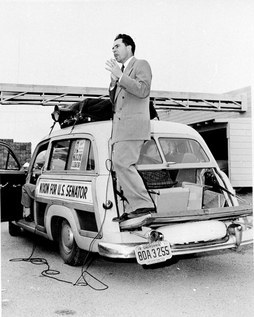 Using the bumper of his car as his podium, Rep. Richard Nixon, R-Ill., addresses a crowd during his campaign along the California coast, northwest of Los Angeles, for the U.S. Senate nomination on April 22, 1950.  (AP Photo)