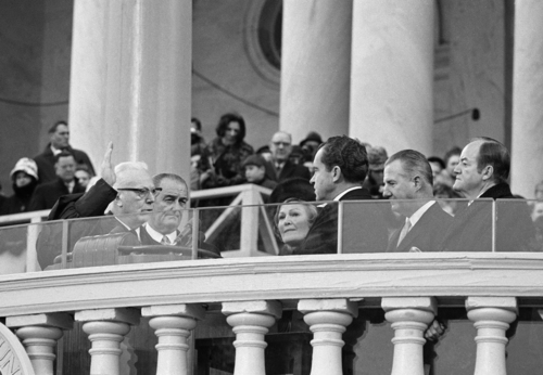 Chief Justice Earl Warren administers oath to President Richard Nixon as his wife, Pat, holds two family bibles and former President Lyndon Johnson watches ceremony on U.S. Capitol steps on Jan. 20, 1969 in Washington.   Vice President Spiro T. Agnew is at right of Nixon and former Vice President Hubert H. Humphrey is at right. Thick bullet proof glass rings front of the stand as part of the tightest security ever given an inauguration. (AP Photo)